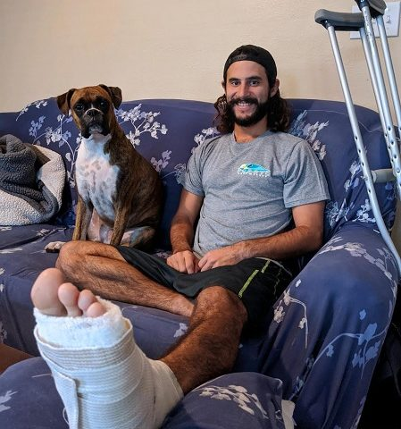 Stephen Michelena shows his shark bitten foot, while his dog Sophie watches over him.